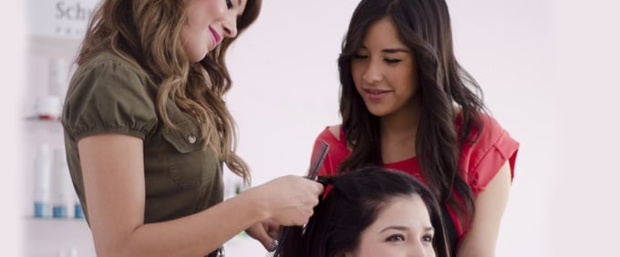 An instructor teaching a student about styling at Raphael's Beauty School