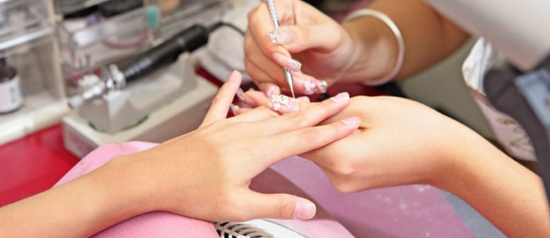 Student getting real nail technician experience manicuring a client's nails in a working salon