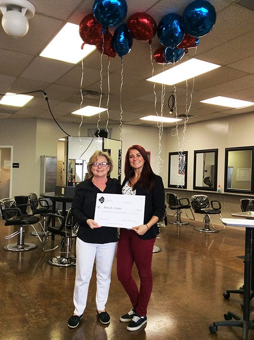 Our 2015 summer scholarship winner is Mary Cooper. In this picture she is being presented with the scholarship certificate and there are red and blue helium-filled balloons floating at the ceiling with ribbons hanging down.