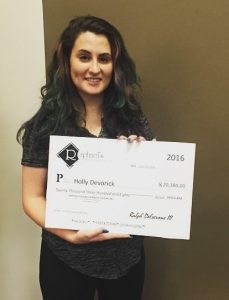 Holly Devorick holding her scholarship at Raphael's.