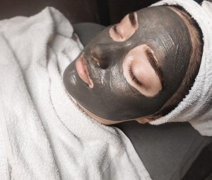 A woman with a face mask in a spa environment.