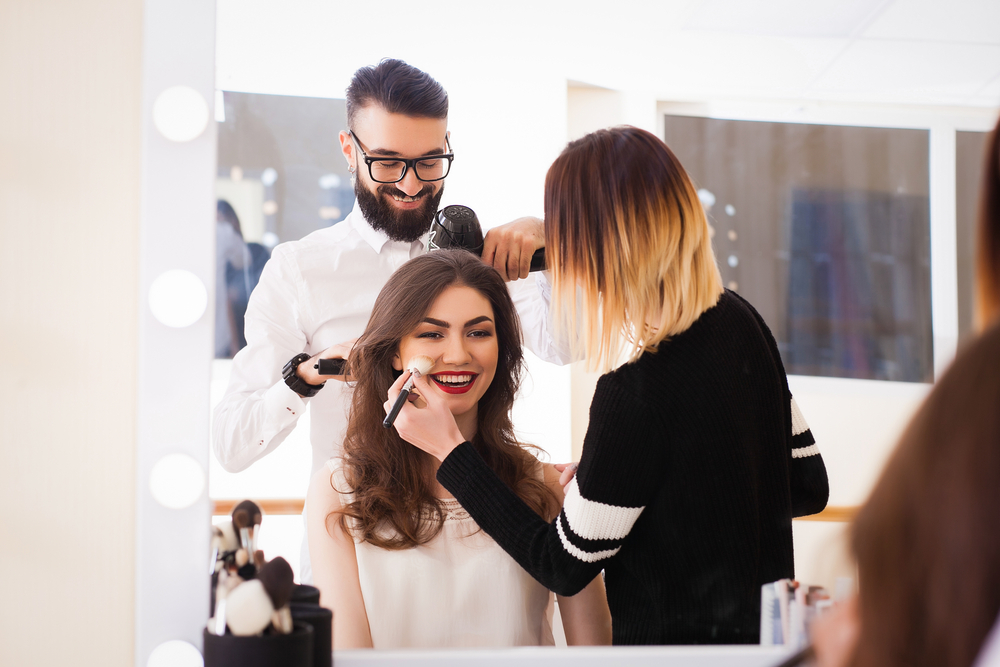 man and woman doing hair and makeup
