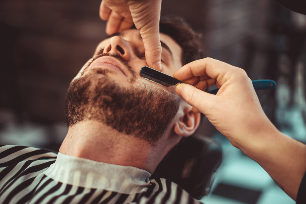 barber shaving a man's beard