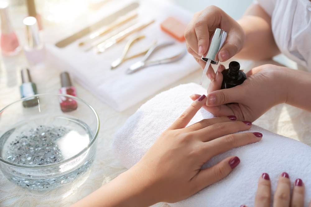 applying nail polish at a manicure station