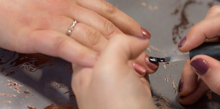 A manicurist painting nails