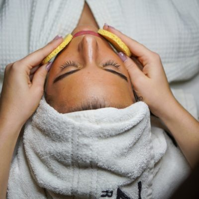 esthetician puts lemon slices on clients face